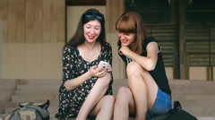 Girl shows her friend funny photos on the phone and discuss it Stock Footage