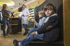 Two brothers waiting whilst mother is talking to pharmacist in a drugstore Stock Photos