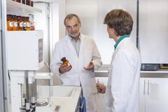 Pharmacist advising trainee on medicine in pharmacy - stock photo