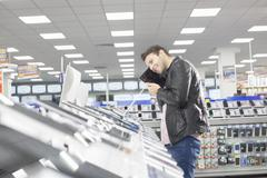 Young male shopper holding up chosen digital tablet in electronics store Stock Photos