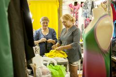 Two seamstresses preparing garments for sewing in workshop - stock photo