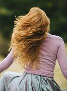Rear view of young woman with long red hair twirling in park - stock photo