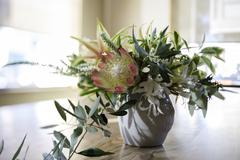 Flower arrangement with foliage on dining room table - stock photo