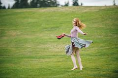 Portrait of young woman dancing in park holding red high heels - stock photo