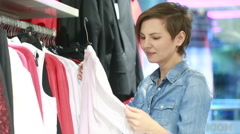 Pretty elegant woman shopping in clothes store Arkistovideo