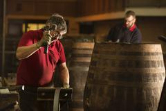 Male cooper using hammer in cooperage with whisky casks - stock photo