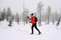 Young woman nordic walking in snow covered forest, Posio, Lapland, Finland - stock photo