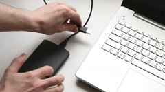 A young man plugging hard disk drive in the notebook computer Stock Footage