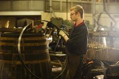 Male cooper making whisky casks in cooperage - stock photo