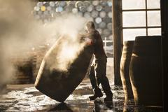 Male cooper working in cooperage with whisky casks - stock photo