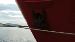 Bow of red metal ship with rusty anchor moored at harbor dock. Stock Footage