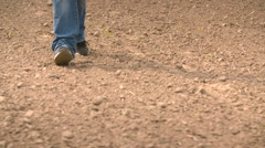 Farmer walks out onto his field and finds hard caked ground after a long dry Stock Footage