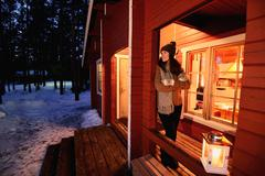 Portrait of young woman looking out from cabin porch at night, Posio, Lapland, - stock photo