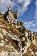 Mountain biker carrying bike, Valais, Switzerland - stock photo