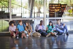 Six higher education students sitting on floor Stock Photos