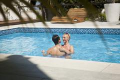 Heterosexual couple in swimming pool together, face to face - stock photo