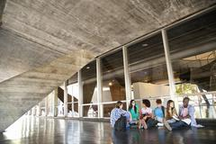 Higher education students sitting on floor - stock photo