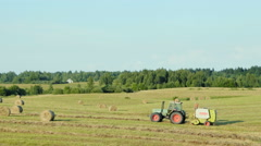 Tractor collects and makes bales of hay - stock footage