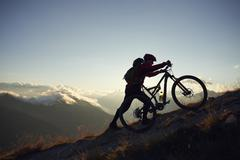 Mountain biker pushing bike uphill, Valais, Switzerland - stock photo