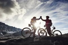 Mountain bikers shaking hands, Valais, Switzerland - stock photo