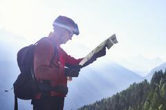 Mountain biker holding map, Valais, Switzerland - stock photo