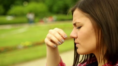 Young, sad, lonely beautiful woman face in the park  Stock Footage