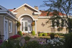 Beige brick house exterior with front door portico and flower bed garden - stock photo