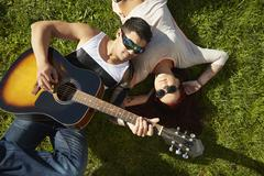 Overhead view of young couple lying on grass playing acoustic guitar Stock Photos
