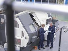 Senior engineer instructing apprentice on factory machinery, high angle view Stock Photos