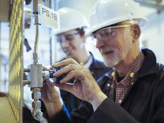 Senior and apprentice engineers adjusting pipework in power station - stock photo