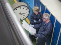 Senior engineer instructing apprentice in factory, high angle view Stock Photos