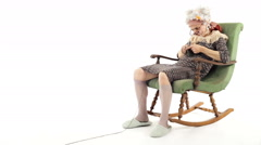 Funny grandmother is knitting on rocking chair isolated on white - stock footage