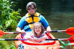 Father and child kayaking in summer - stock photo
