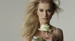 Portrait of a beautiful sexy blonde woman holding white rose. - stock footage