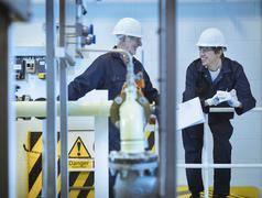 Senior and apprentice engineers talking in power station Stock Photos