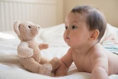 Baby boy lying on front, with teddy bear beside him - stock photo