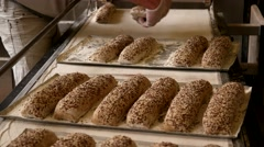 Bakers putting the raw baguettes with seeds to the baking sheet Stock Footage