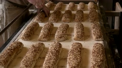 Bakers in gloves making patterns on raw baguettes with seeds using a blade Stock Footage