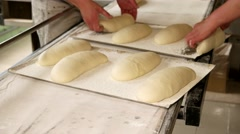 Bakers putting the raw bread to the baking sheet. Stock Footage