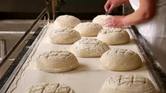 Female baker making traditional pattern on the raw ball dough bread. Bakehouse Stock Footage