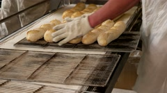 Baker taking out hot fresh baguettes to the tray Stock Footage