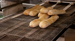 Manufacture of bread, hot white baguette placing to the iron trays, closeup - stock footage