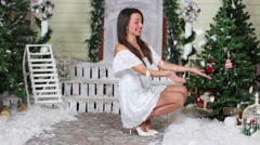 Beautiful girl in white dress throw up snow sitting near the porch Stock Footage