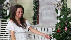 Close-up view of beautiful girl throw up snow sitting near the porch Stock Footage