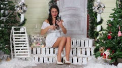 Beautiful girl with headphones sitting on porch and correct hairstyle Stock Footage