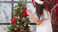 Girl in cap seeking place for hangs up toy on the Christmas tree Stock Footage