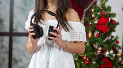 Young girl dancing with headphones in hands near Christmas tree Stock Footage
