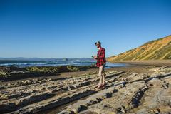 Young man standing on beach looking at ocean - stock photo