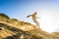 Young man running down sandy hill - stock photo