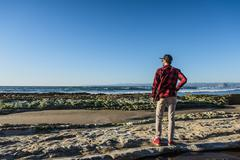 Young man standing on beach looking at ocean, rear view Stock Photos